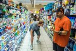 Youth bending down to see contents on store shelves